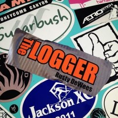 The Logger Duct Tape Sticker On Top of Other Promotional Stickers